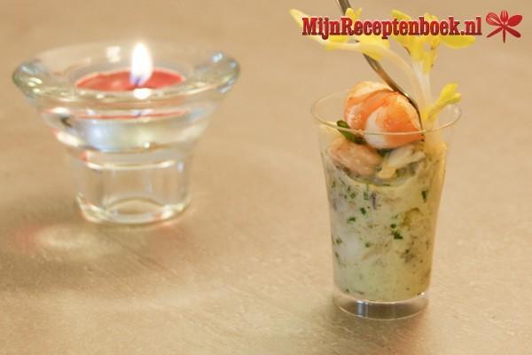 Glaasje gevuld met tartaar van zalm, augurk en mierikswortel